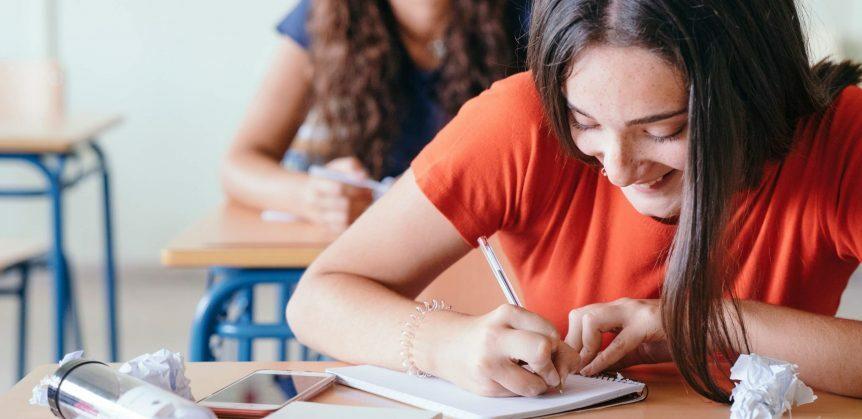 Coesão e coerência: fotografia de uma menina sorrindo enquanto escreve em um caderno em uma sala de aula.