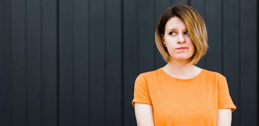 Têm ou tem? Fotografia de uma mulher com uma expressão de dúvida.