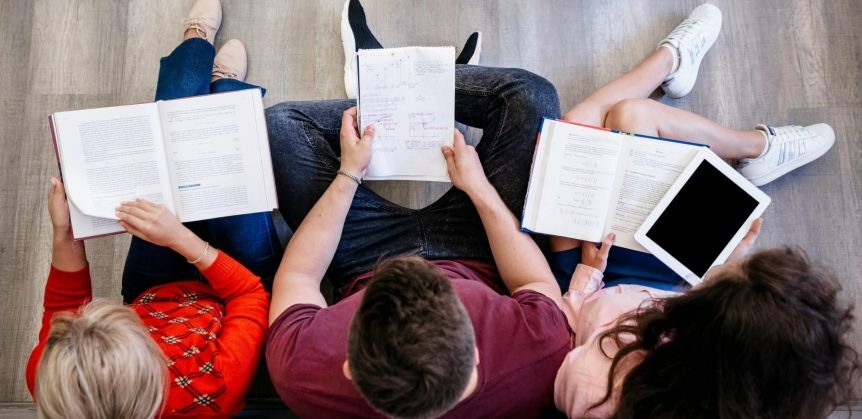 Classificação de sílaba: fotografia tirada de cima de três pessoas estudando, elas estão com cadernos e livros no colo.