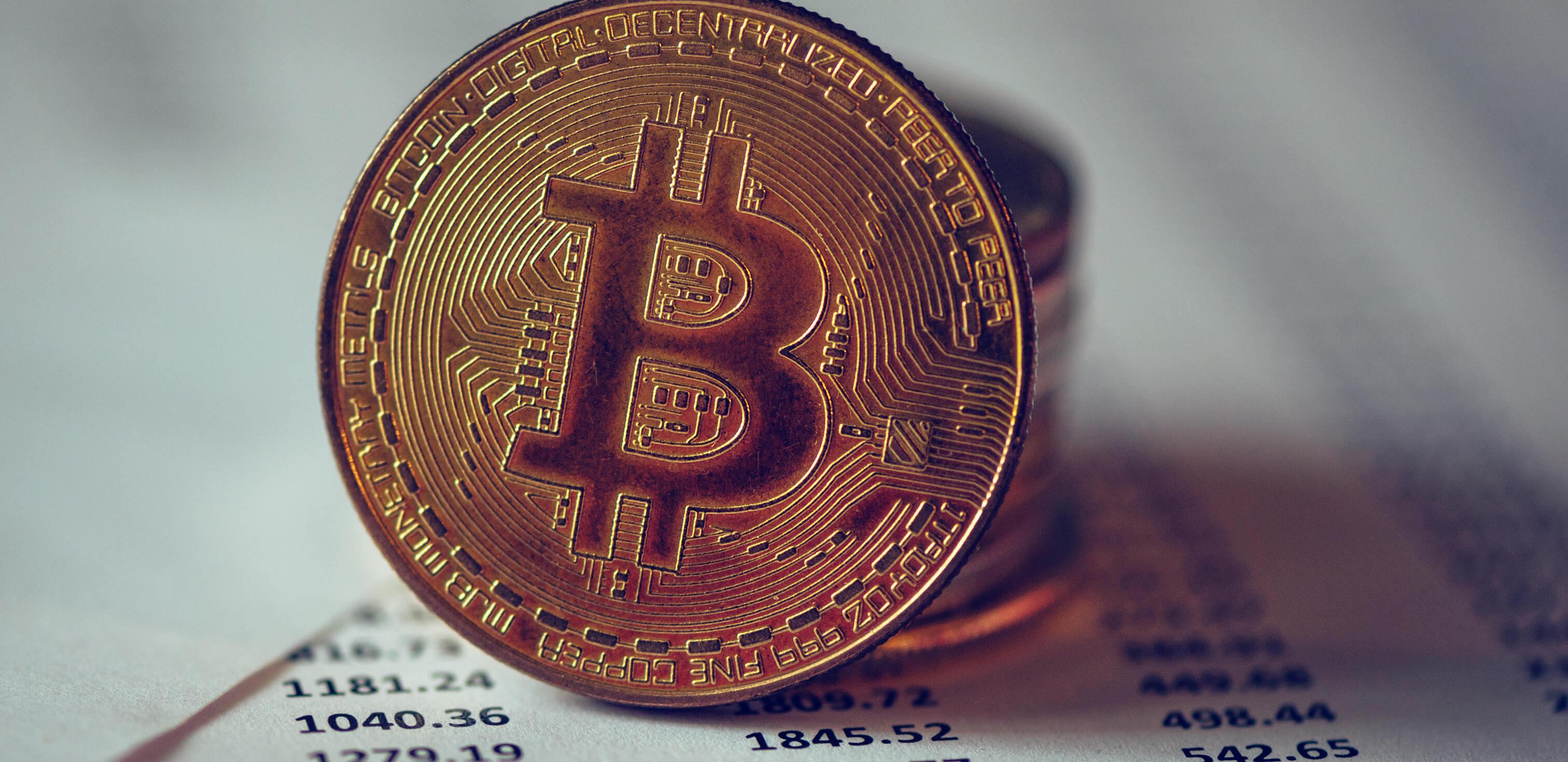 Redação sobre moedas virtuais: fotografia de uma moeda com o símbolo da Bitcoin sobre uma folha com diversos números.