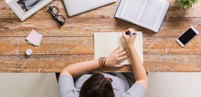 Como começar uma redação - mesa com livro aberto, notebook, celular, fotografia, post-it, óculos e um caderno aberto sendo utilizado por uma pessoa.