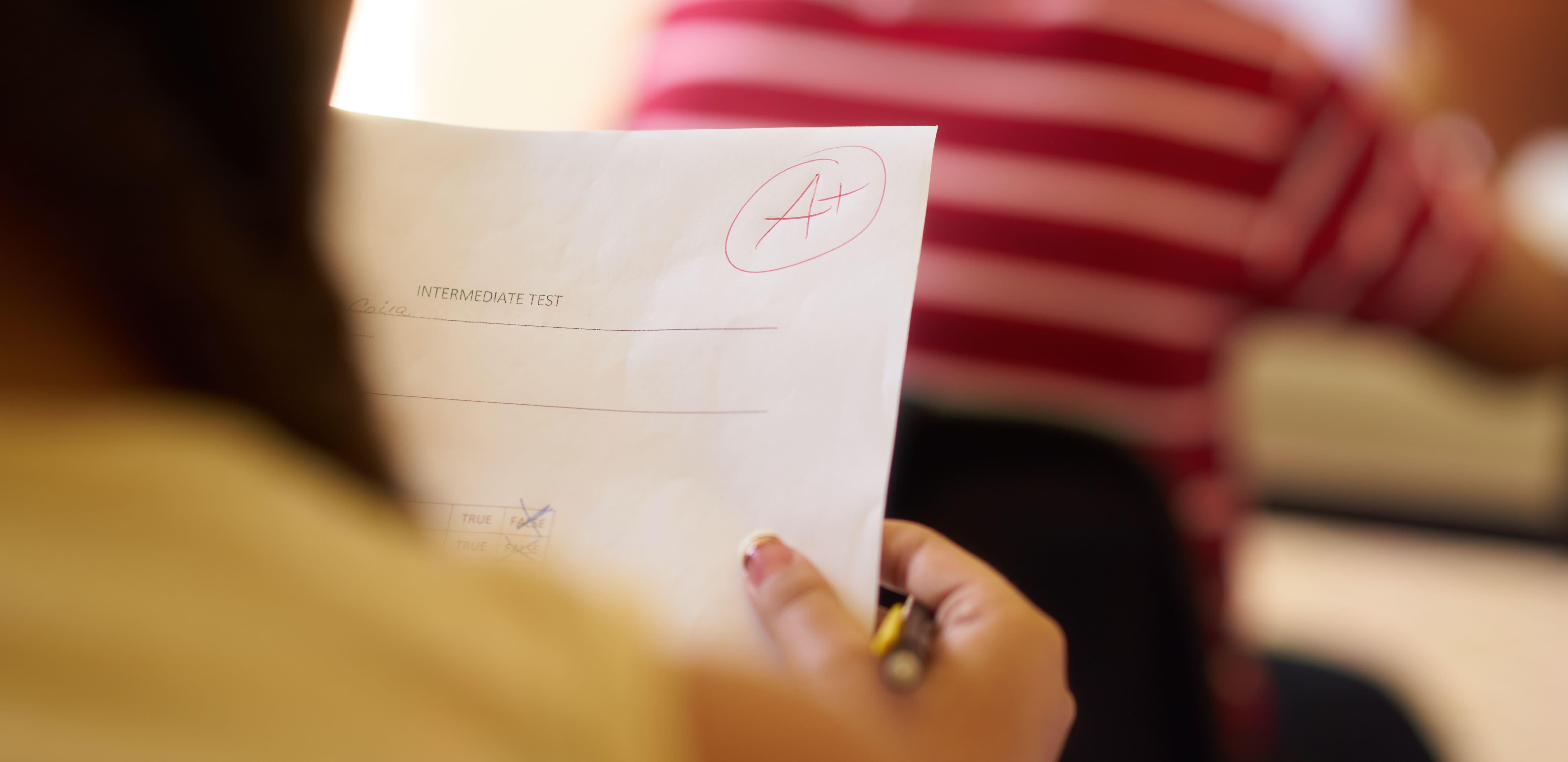 Como se dar bem no enem - imagem de uma menina segurando uma prova com a nota máxima.