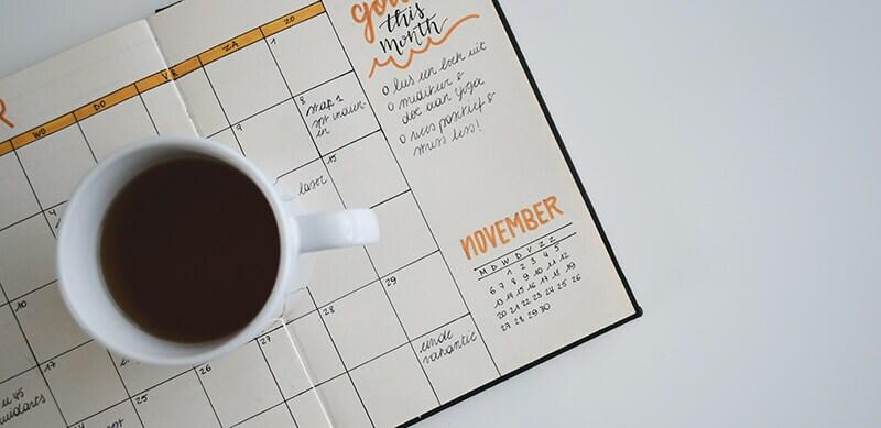 Cronograma Sisu: fotografia de uma agenda com uma xícara de café em cima.