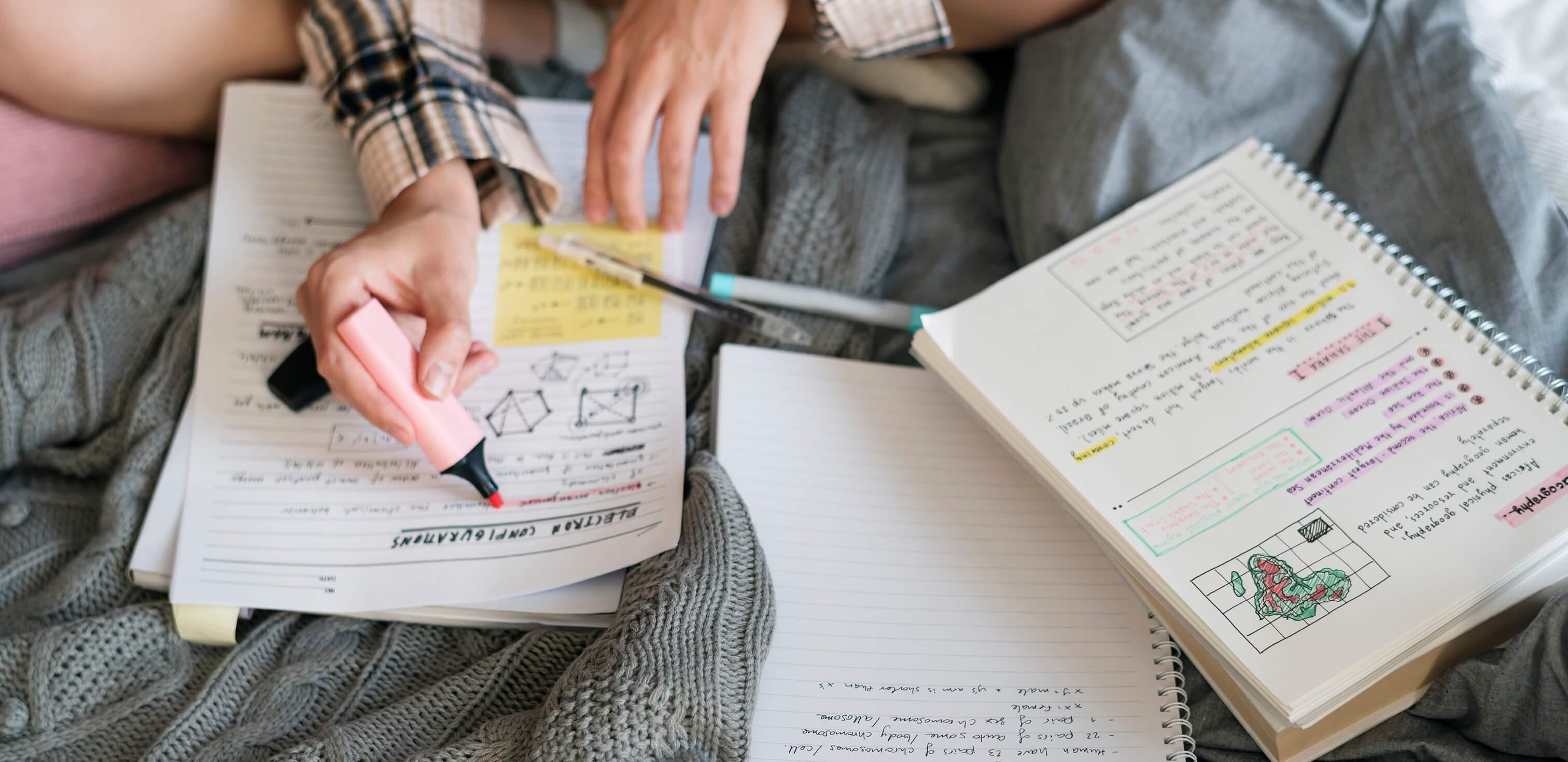 Reta final pro Enem: fotografia de uma mulher estudando e fazendo marcações em vários livros em cima de uma cama.