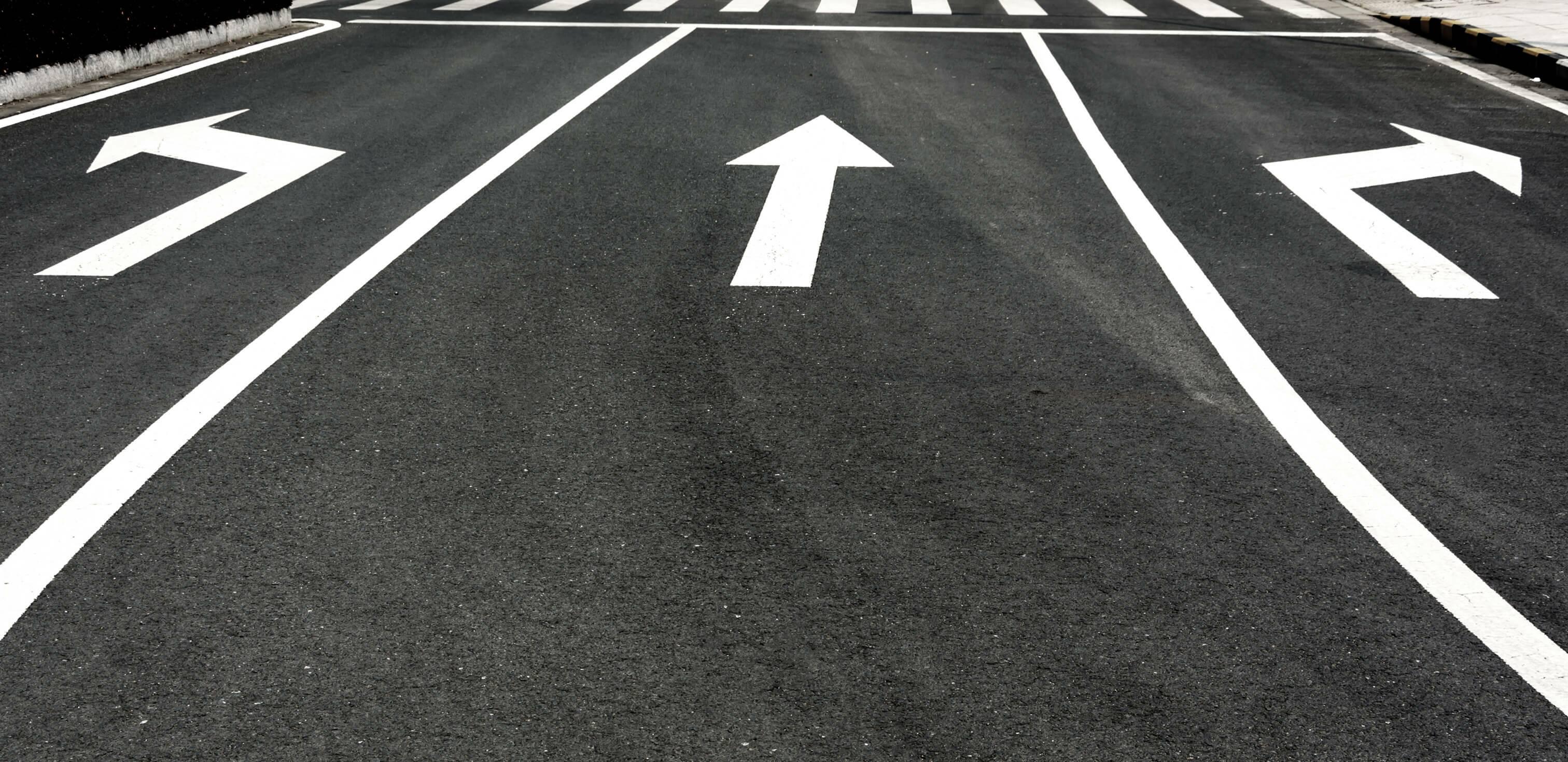 Teste vocacional: fotografia de uma rua asfaltada pintada com uma seta para a direita, uma para frente e uma para a esquerda.