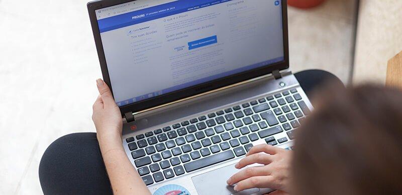 Documentos ProUni: fotografia de uma mulher mexendo no notebook acessando o site do ProUni.