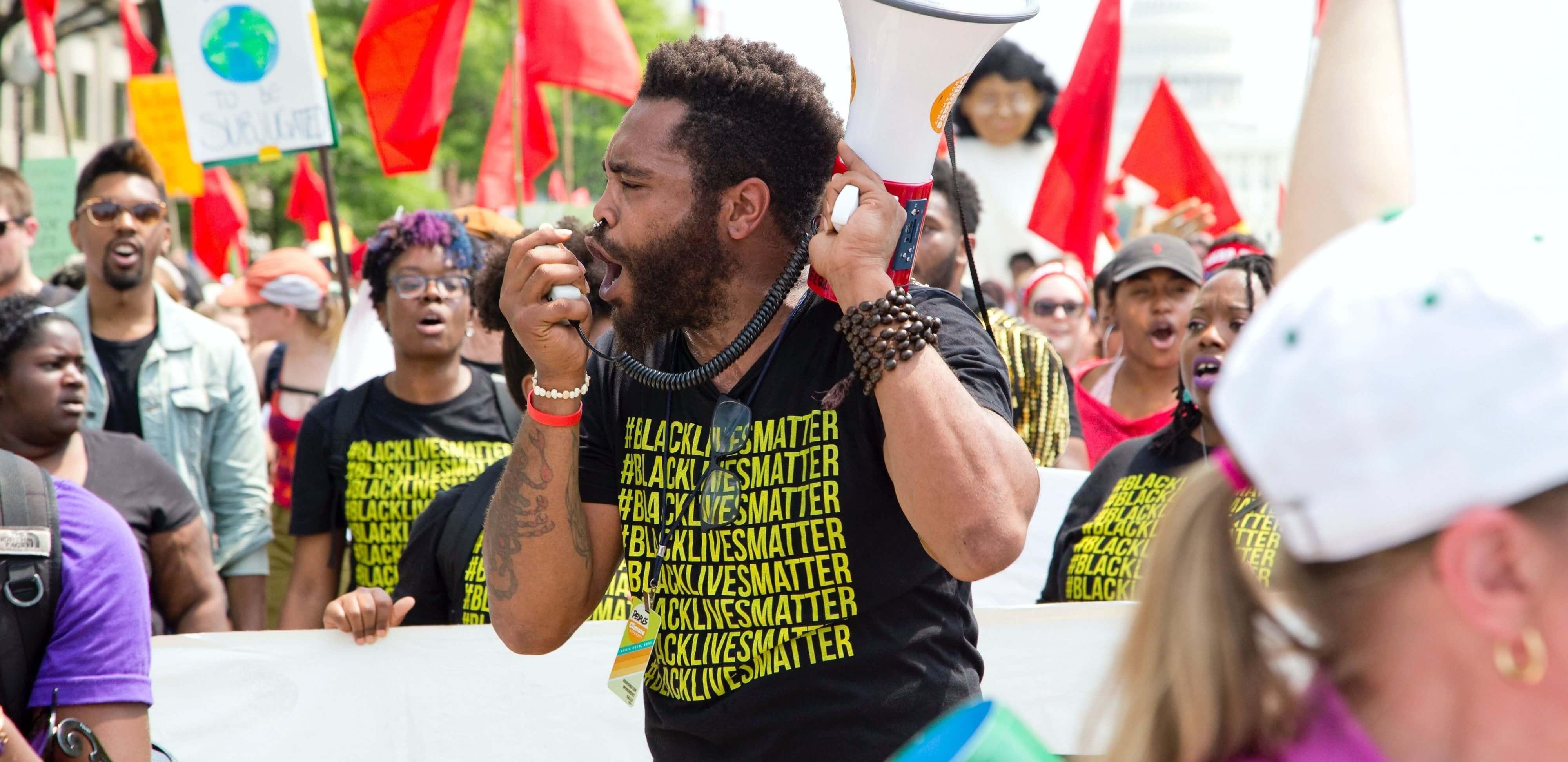 black lives matter: imagem de manifestantes à rua, em destaque manifestante negro