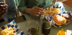 Problemas relacionados à alimentação no século XXI: fotografia de duas pessoas comendo sanduíches com batata frita.