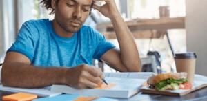 Como fazer fichas de estudo: imagem de um estudante fazendo anotações em pequenas fichas de estudo.