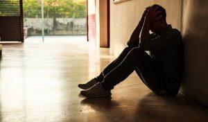 O aumento da depressão entre os jovens no Brasil: imagem de um jovem sentado com as mãos na cabeça
