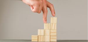 Nota de corte: imagem de uma mão subindo os dedos médio e indicador em uma escadinha feita de cubos de madeira.