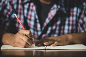 Diferença entre tema e assunto: imagem de um menino escrevendo num caderno