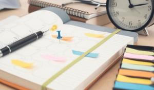 4 dicas de como montar um cronograma de estudos e organizar a sua rotina: um caderno, uma caneta e um relógio ao fundo.
